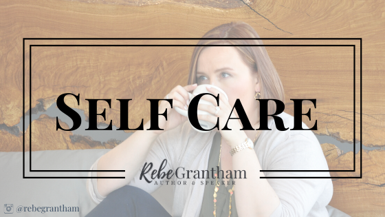"""photo of me drinking tea sitting up against a live-edge wooden headboard. The words """"self care"""" and my logo are superimposed over the image."""